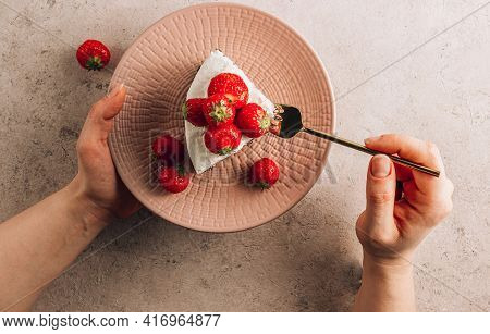 Female Hands Hold A Pink Plate With A Piece Of Chocolate Zebra Cheesecake With Fresh Strawberry On B