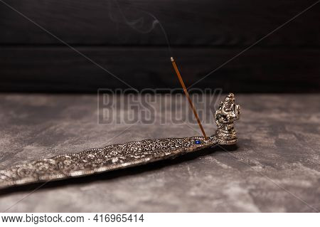 Indian Incense Sticks Smoke In A Stand On Gray Background. Incense Stick Burning On A Metal Stand. C
