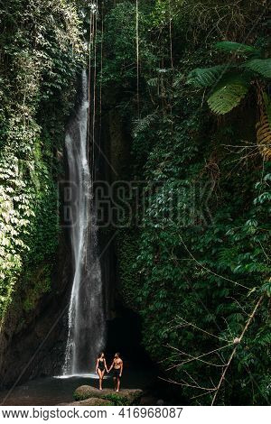 Couple At A Tropical Waterfall. A Woman And A Man At A Beautiful Waterfall. Vacation On A Tropical I