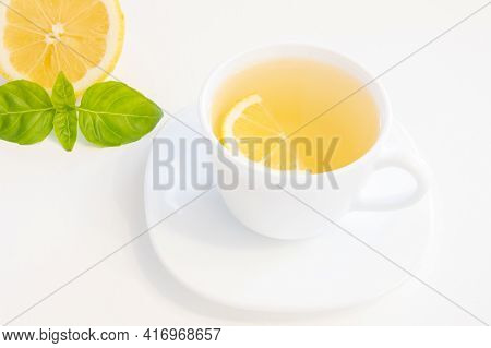 Cup Of Green Tea With Lemon Slice, Basil And Mint Isolated On White Background