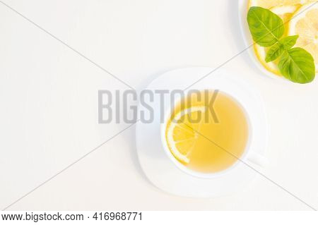 Cup Of Green Tea With Lemon, Basil And Mint Shoot From Above Isolated On White Background With Copy