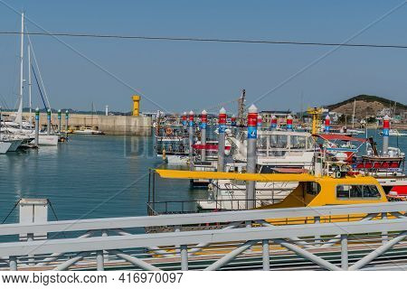 Pyeongtaek, South Korea; April 6, 2021:row Of Yachts And Tour Boats Docked At Jeongok Marina With Ye