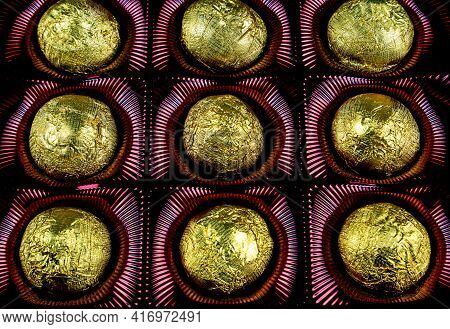 A Box Of Chocolates In A Golden Foil Wrapper. Sweets In Shiny Foil. Golden Color. Sweet Dessert. Box