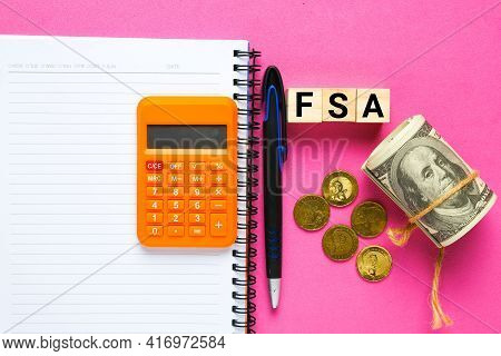 Wooden Block Written Fsa Or Flexible Spending Account With Medical Toy, Fake Money And Notebook. One