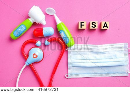 Wooden Block Written Fsa Or Flexible Spending Account With Medical Toy And Face Mask On Pink Backgro