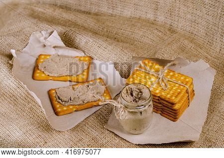 Rectangular Crackers And A Glass Jar Of Liver Pate On Sackcloth. Close-up Of Crispy, Salty, Ready-to