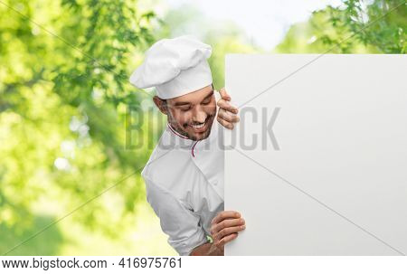 cooking, culinary and people concept - happy smiling male chef in toque with big white board over green natural background