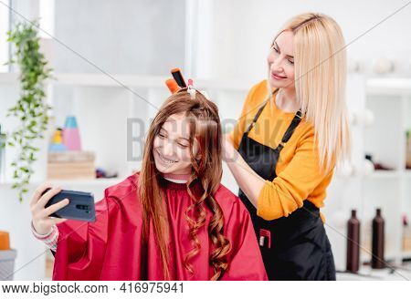 Beautiful young girl making selfie with hairdresser during hairstyle process. Curls hairdo for long hair