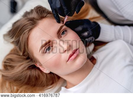 Permanent makeup master finishing beautiful eyebrows blond microblading for model girl. Closeup portrait