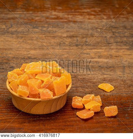 dried mango fruit diced - small wooden bowl on a weathered wood background