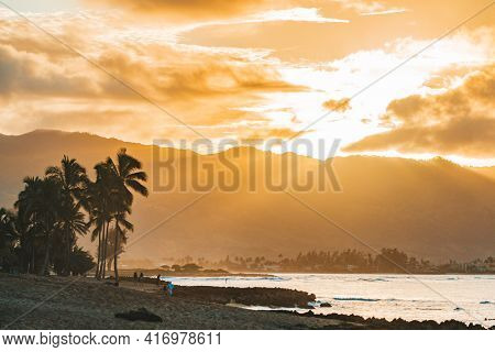 Hawaii beach travel landscape. Tourist destination in Big Island, Oahu, USA summer vacation. Sunset against silhouette of palm trees and people paddle surfing.