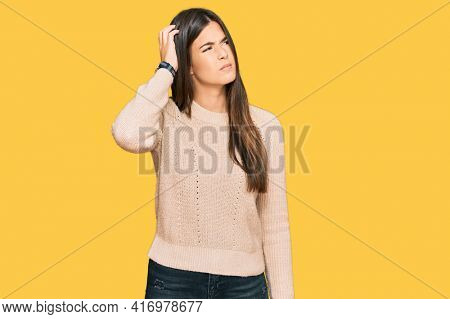 Young brunette woman wearing casual winter sweater confuse and wondering about question. uncertain with doubt, thinking with hand on head. pensive concept.
