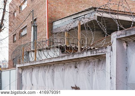 Barbed Wire Above Concrete Fence Of Prison. Wall. Security. Control. Danger. Limitation. Forbidden.