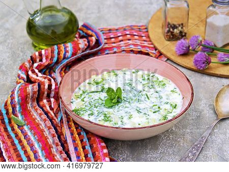 Cold Summwr Soup On Ayran Or Natural Unsweetened Yogurt With Cucumber And Herbs In A Pink Plate On A