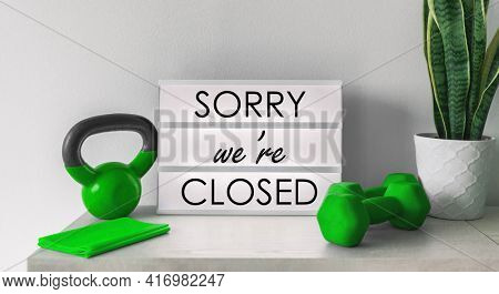 Sorry we are Closed Sign at fitness center gym storefront with training equipment. Shutdown curfew order of restaurants, non essential businesses forcing to bankruptcy with the closing. Coronavirus.