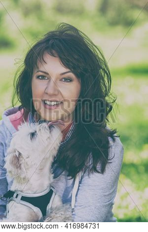 Small white maltese dog licking his owner during walk in park