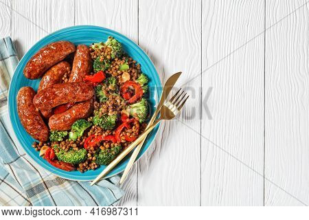 Italian Pork Sausages Braised With Brown Lentils, Red Pepper, And Broccoli On A Blue Plate On A Whit