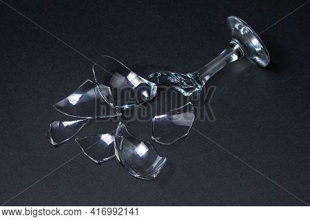 Broken Wine Glass On A Dark Background. Shards Of A Wine Glass On A Black Background. Broken Dishes