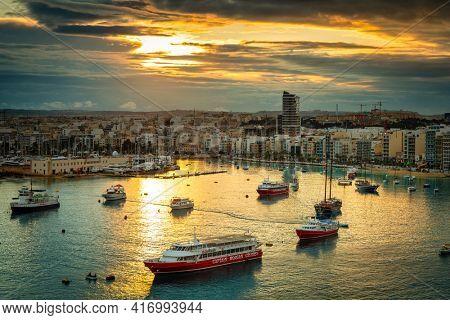 Valletta, Malta - January 11, 2019: Tourists boats in the harbor of Sliema on Malta at sunset.
