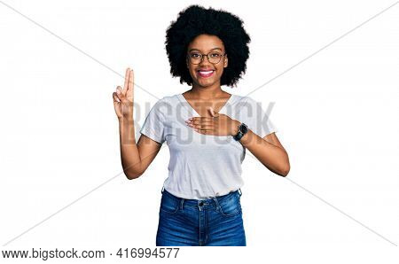 Young african american woman wearing casual white t shirt smiling swearing with hand on chest and fingers up, making a loyalty promise oath