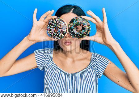 Beautiful young woman holding tasty colorful doughnuts on eyes skeptic and nervous, frowning upset because of problem. negative person.