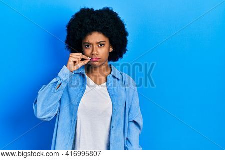 Young african american woman wearing casual clothes mouth and lips shut as zip with fingers. secret and silent, taboo talking