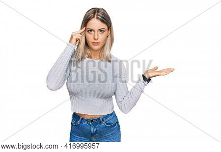 Beautiful blonde woman wearing casual clothes confused and annoyed with open palm showing copy space and pointing finger to forehead. think about it.