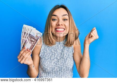 Young caucasian blonde woman holding egyptian pounds banknotes screaming proud, celebrating victory and success very excited with raised arm
