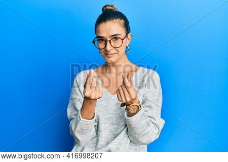 Young hispanic woman wearing casual clothes doing money gesture with hands, asking for salary payment, millionaire business