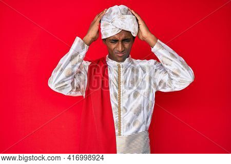 Handsome indian man wearing tradition sherwani saree clothes suffering from headache desperate and stressed because pain and migraine. hands on head.