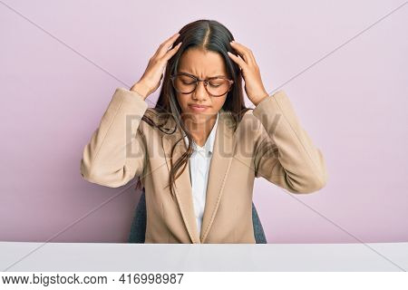 Beautiful hispanic woman working at the office suffering from headache desperate and stressed because pain and migraine. hands on head.