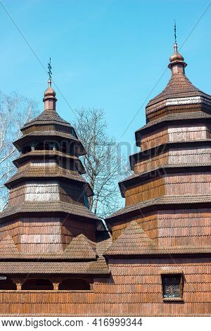 An Ancient Wooden Church And Domes Against The Background Of The Sky And Trees, A Historical Monumen