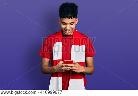 Young african american man football hooligan cheering game holding smartphone smiling with a happy and cool smile on face. showing teeth.