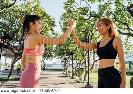 Two Young Asian Female Athlete Friends Shaking Hands In Morning. Beautiful Women Jogging And Running