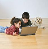 two kids and a dog with laptop computer on the floor poster