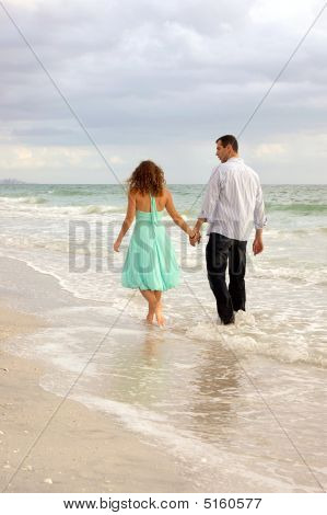 Couple On Beach Walking Away From Viewer