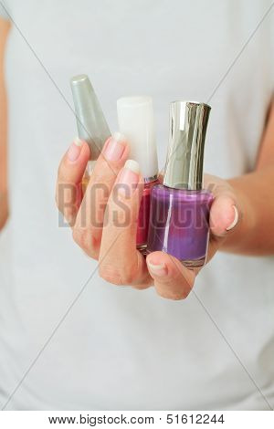 Female Hand With Nail Varnish Bottles
