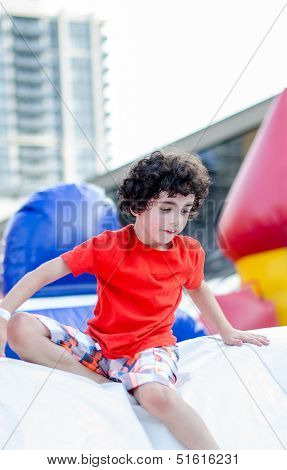 Child Playing In Inflatable Playground