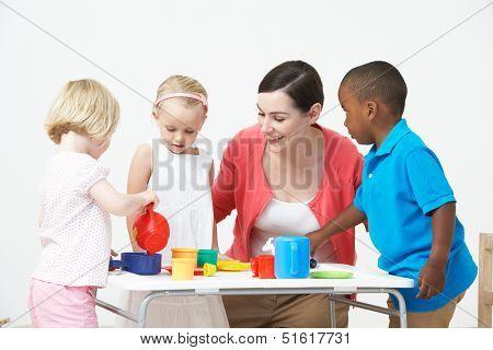 Pre School Children Enjoying Tea Party With Teacher