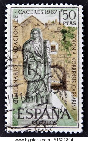 A stamp shows a picture of a Roman matron and the Arc of Christ in Caceres