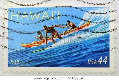 A stamp printed in USA dedicated to Hawai'i Statehood shows surfer and two people rowing a canoe