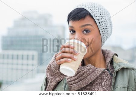 Happy young model in winter clothes enjoying coffee outside on a cloudy day