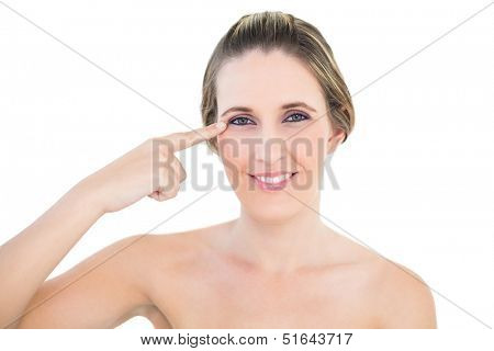 Smiling woman pointing at her eye against white background