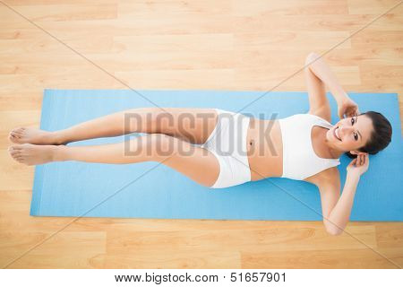 Fit woman doing abdominal crunches and smiling at camera at home on wooden floor