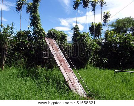 Rusted slide in overgrown grass in Heredia Costa Rica. poster
