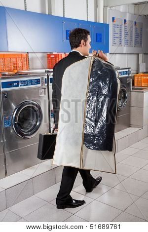 Rear view of young businessman with suitcase and suitcover walking in laundry