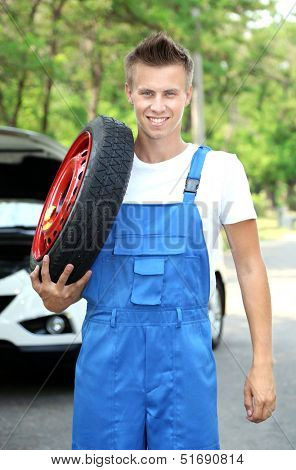 Auto mechanic with tire on his shoulder