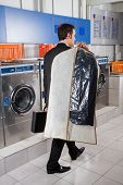 Rear view of young businessman with suitcase and suitcover walking in laundry poster