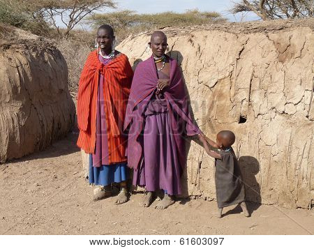 Masai parents with child tugging at mother's clothes for attention