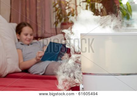 Girl Reading Book On The Background Of Humidifier